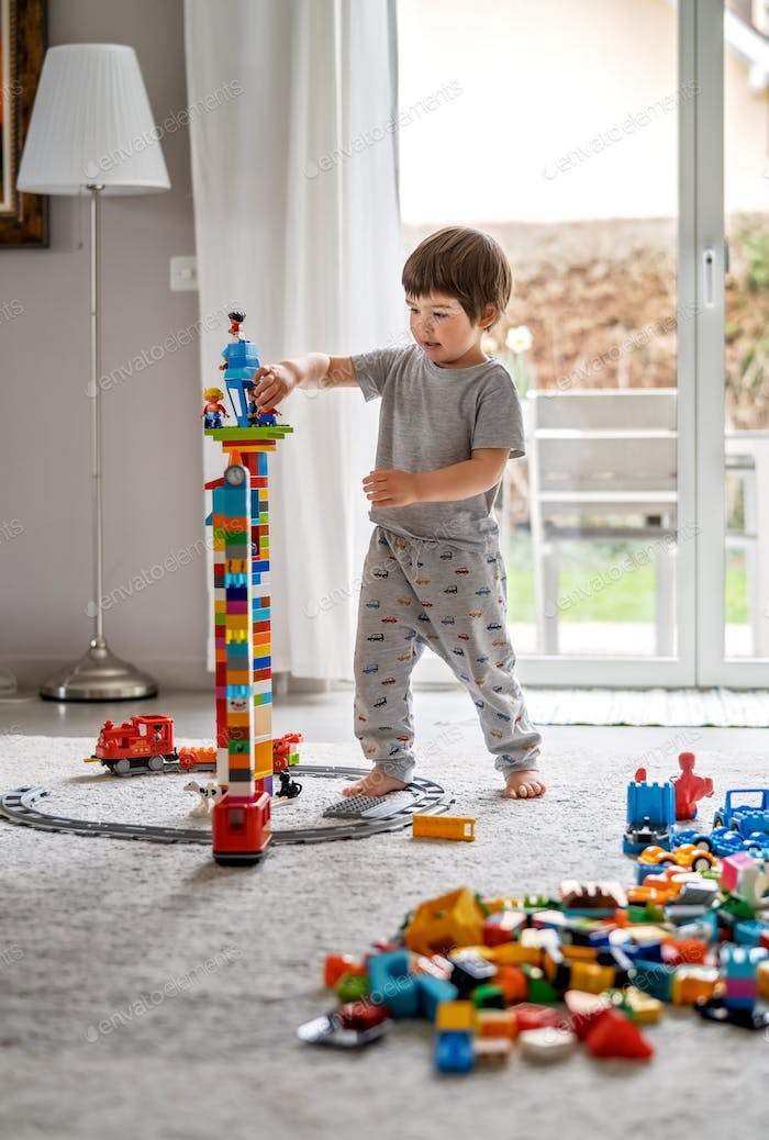 Little toddler boy playing with Lego blocks at home at quarantine isolation period during coronaviru