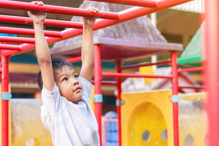Kid exercise for health and sport. Happy Asian child boy play and hanging from bar at the playground