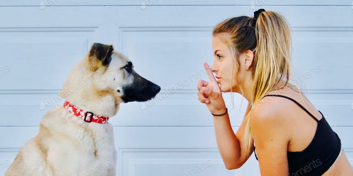 A girl telling secrets to her pet puppy dog and telling her to be quiet and keep it a secret
