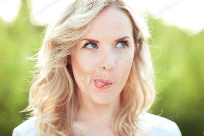 Young blonde girl making faces outdoors. Looking up. Having fun.