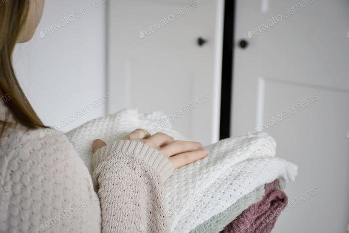 Young woman is tidying up her knitted sweaters