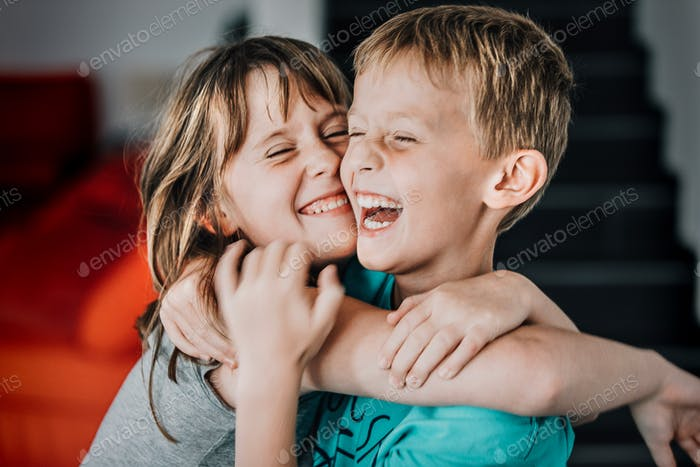 Candid portrait of young boy and young girl having fun hugging each other and laughing out loud.