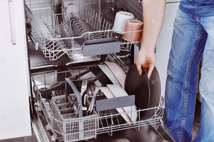 man doing chores; loading dishwasher; putting plate into dishwasher; in the kitchen; close up