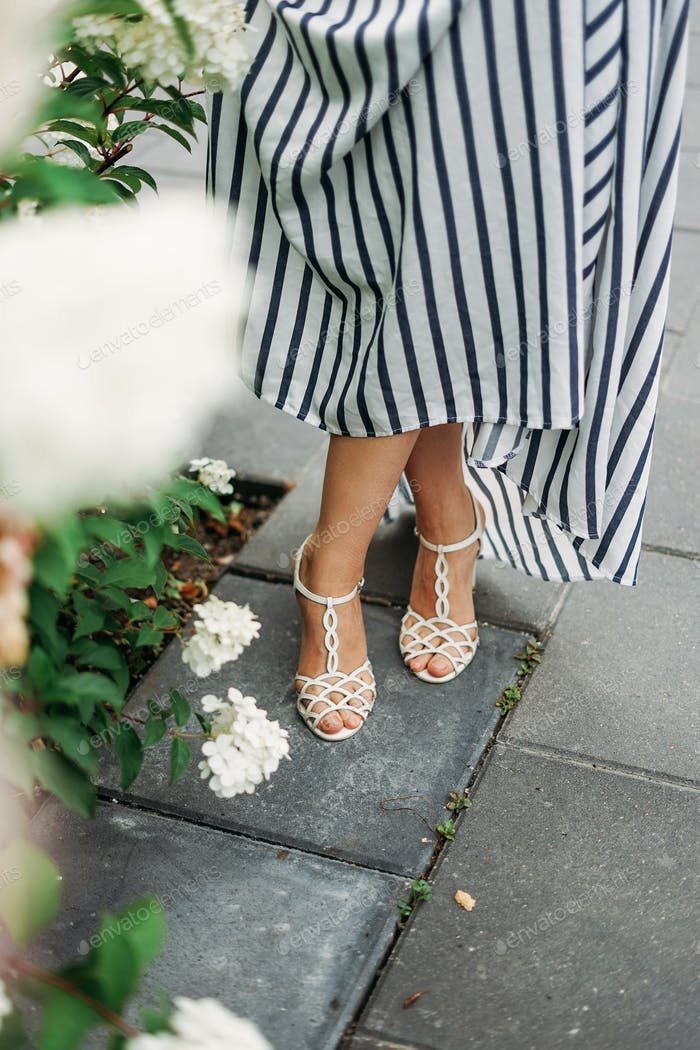 Women's feet in a long dress and white sandals