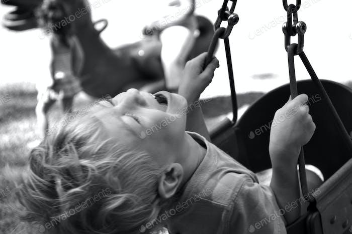 Die pure Freude Aufregung des Kindes lachen beim Schwingen auf einer Schaukel auf dem Spielplatz. schwarz und weiß