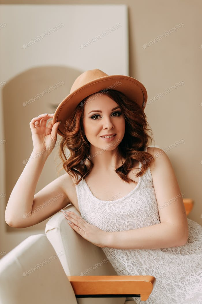 Portrait of a cute beautiful gentle red-haired woman in a hat looking at the camera; lady; person; g