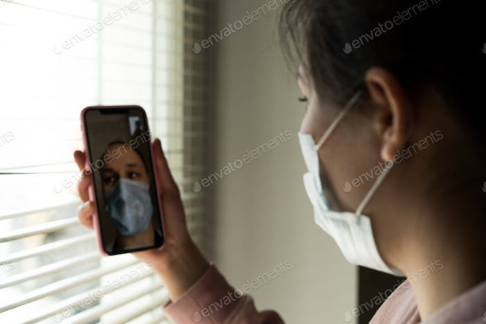 Portrait of a young girl wearing a disposable medical mask, using a  mobile phone for a video call d