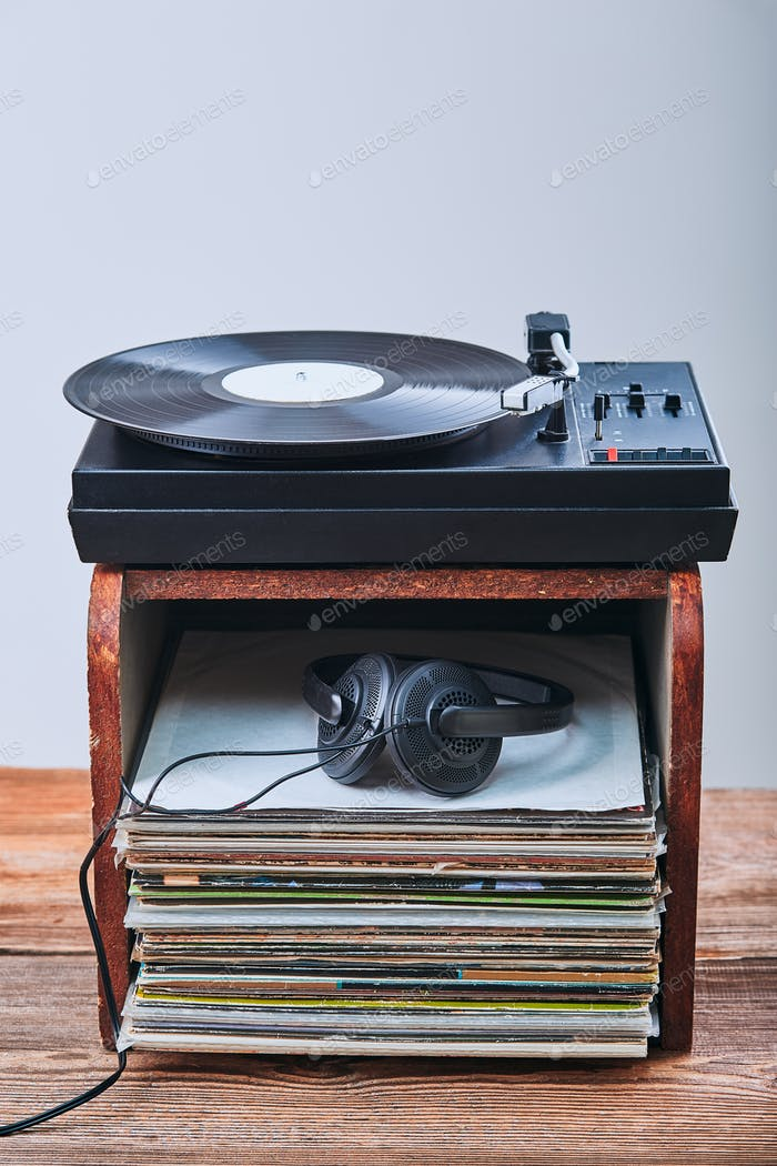 Stack of vinyl records, turntable vinyl player and headphones. Classic stereo set. Vintage style