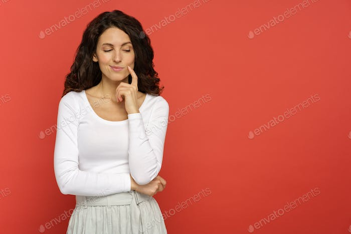 Portrait of female look down with cunning smile tricky think new idea, plan over red wall background