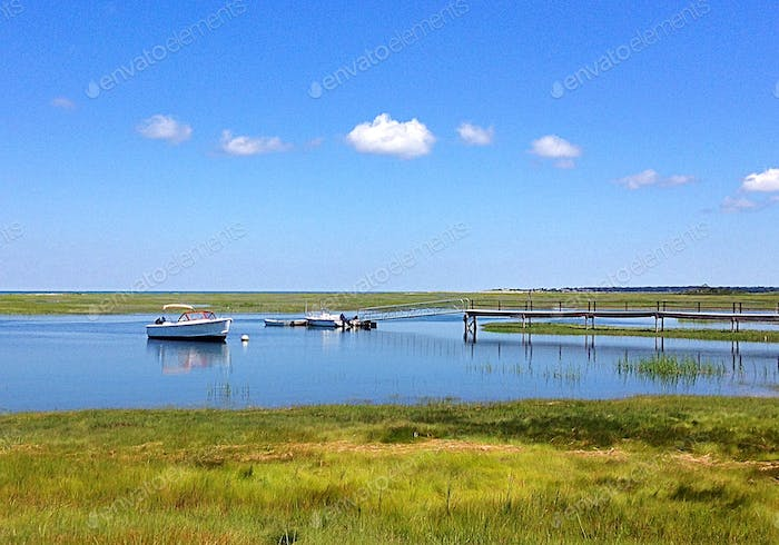 A small inlet with a dock and boats.  Green marsh surrounds the blue water with blue sky overhead.