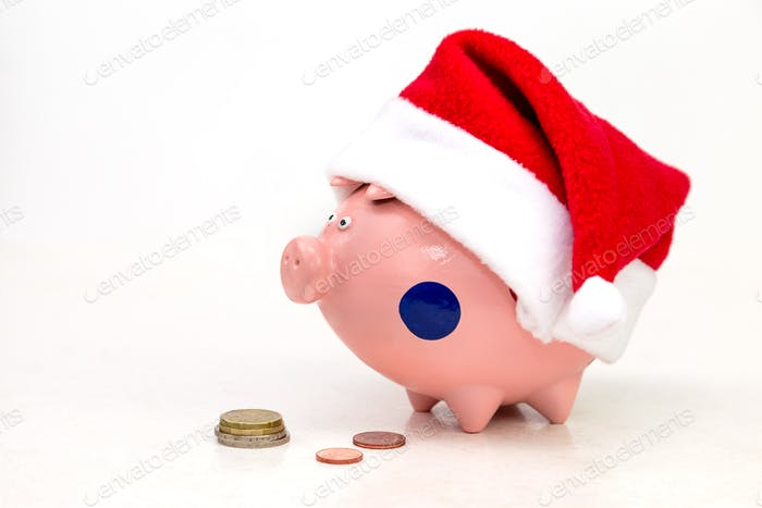 piggy bank in a red cap of Santa Claus and a stack of coins on a white background
