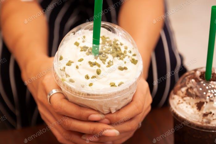 Starbucks Tea Ramisu Frappe mit Schlagsahne in den Händen der Frau