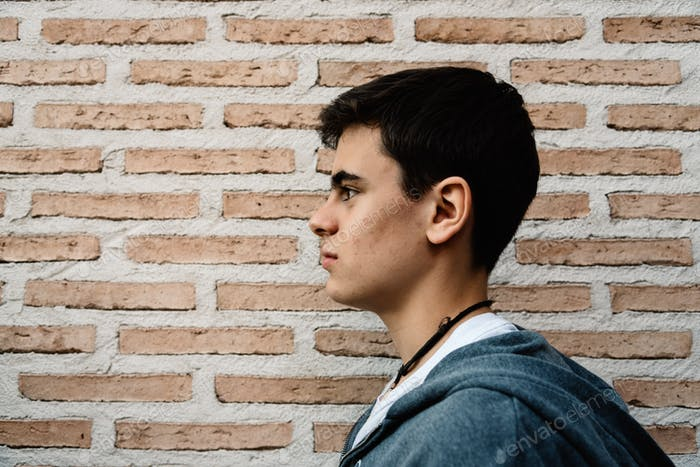 Side head shot of young adult man against brick wall.