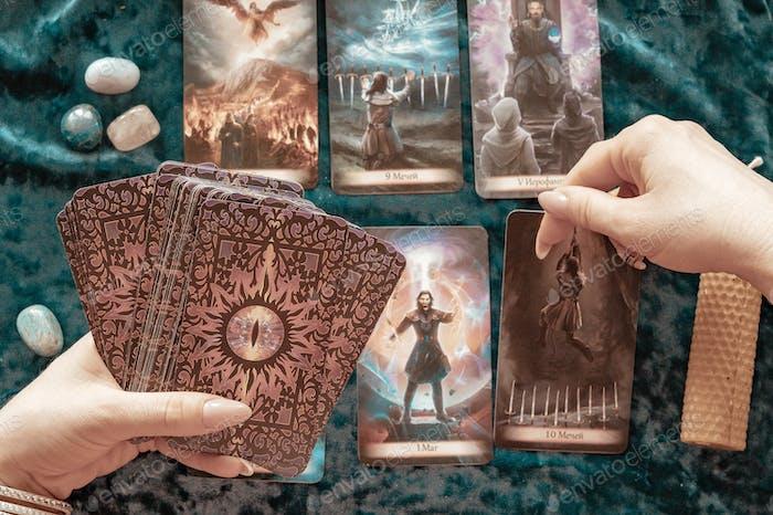 Tarotkarten in den Händen einer jungen Frau, Kerzen und Runen auf blauem Samthintergrund