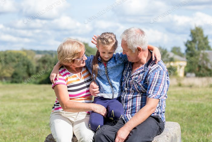 Grandparents having good time with heir granddaughter, smiles and hugs