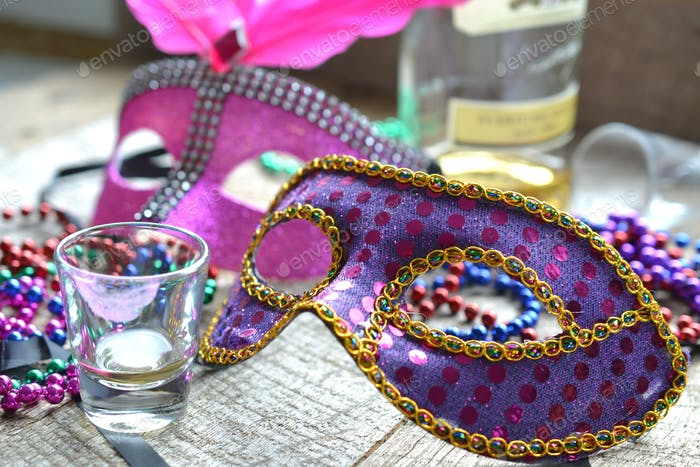 Mardi Gras - purple and pink masks, multicolored beads,  next to liquor bottle and shot glasses