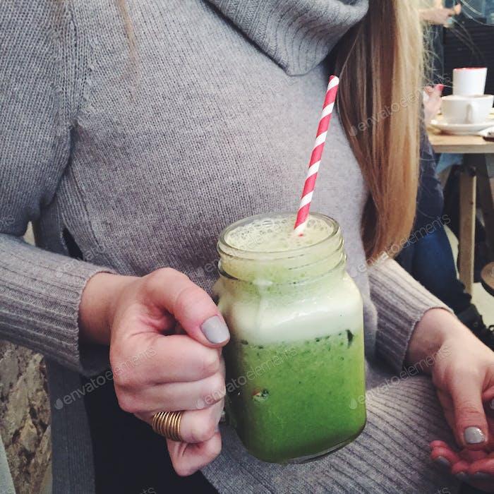 Mädchen im Pullover trinken grünen Saft