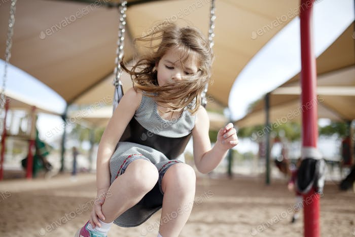 little girl flying on a swing at the park playground swingset