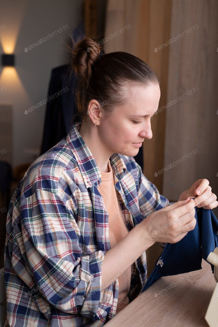 a young woman of European appearance sews