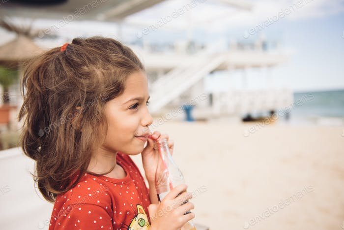 Drinking juice from bottle with straw, on the beach, in summer. There's nothing to care, nothing to