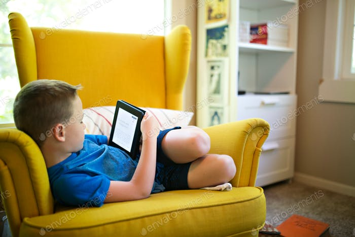 Boy reading on a kindle e-reader on a yellow chair