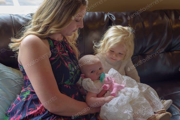Mama mit kleinem Mädchen und Baby am Tauftag