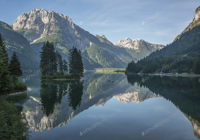 Beautiful forest reflection at the Predil lake with surrounding mountains and an island