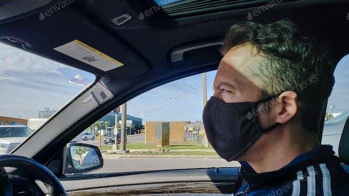 Usar protección facial mientras conduces un coche pensando en la psicología en movimiento.