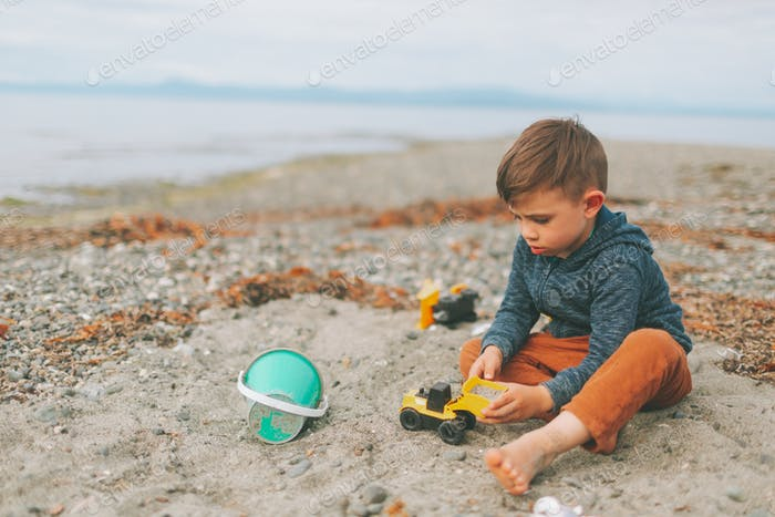 A little boy digging in the sand at the beach.