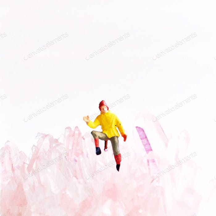 Tiny model scale hiker sitting in a pink quartz cluster against a white background.