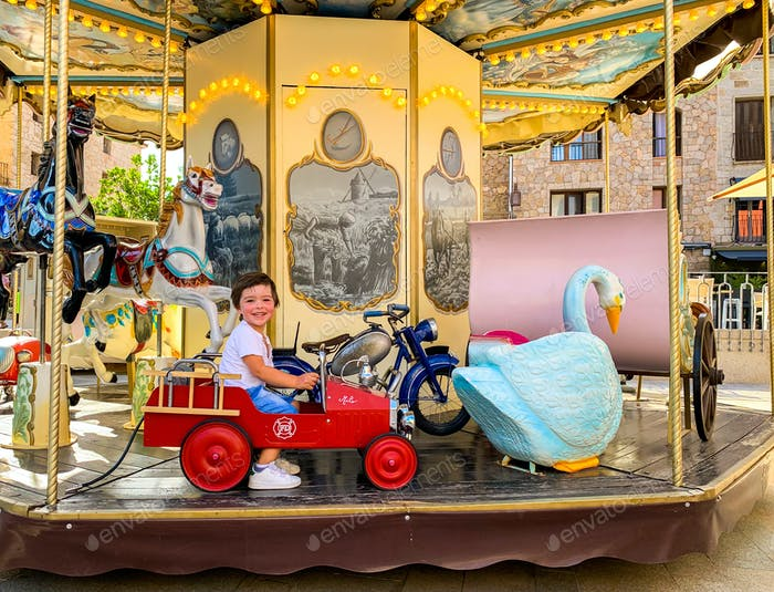 Happy little toddler boy enjoying riding merry go round alone during coronavirus pandemic
