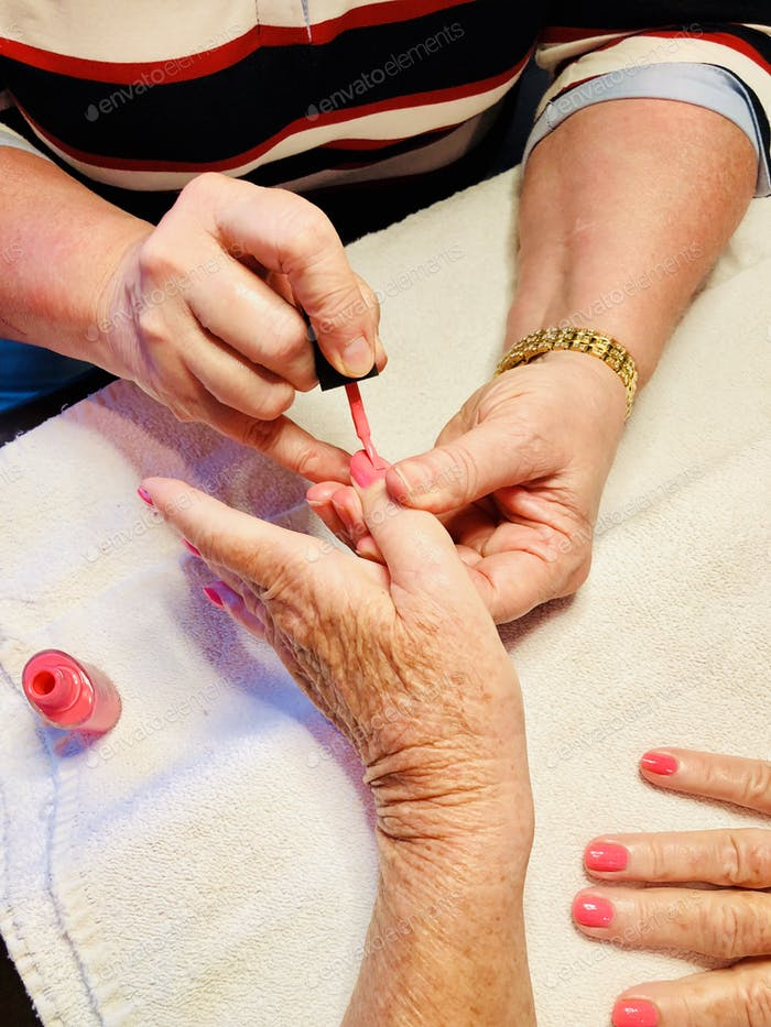 Manicurist applying pink nail polish on a clients.