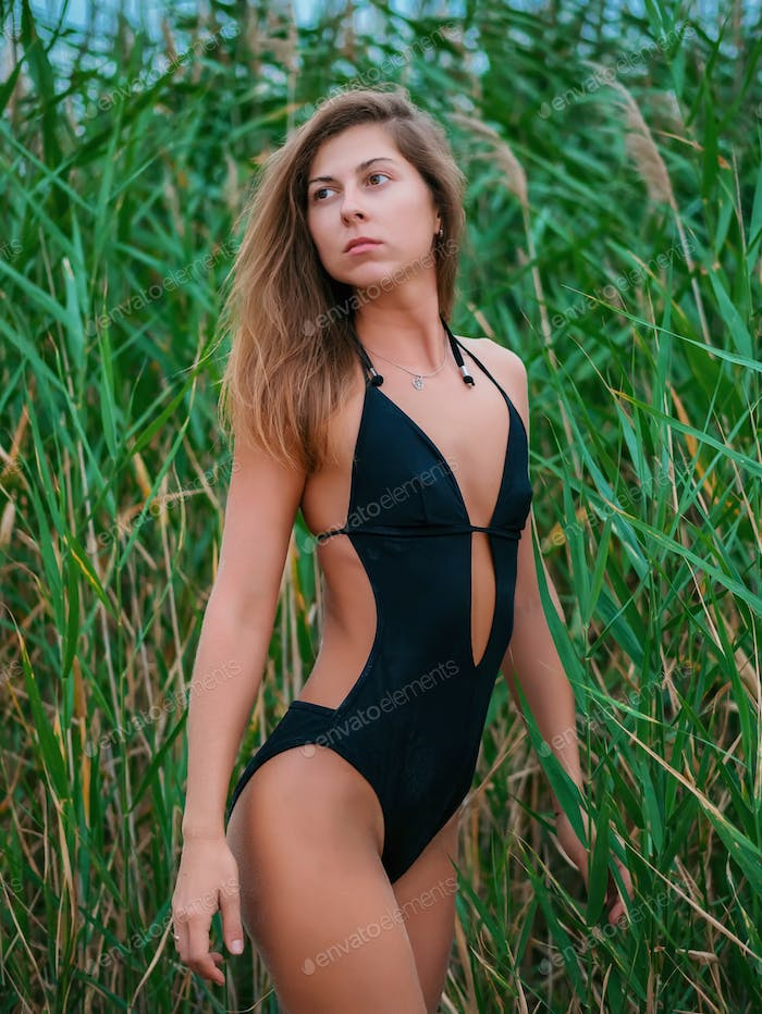 Beautiful woman in swimsuit standing in reeds