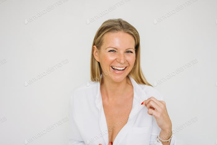 Portrait of happy blonde forty year woman with long hair in white shirt on white wall background
