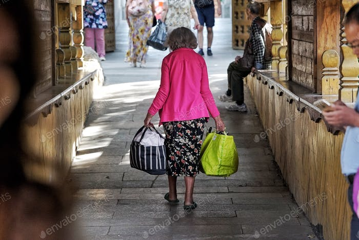 Old woman carrying heavy bags at the fair