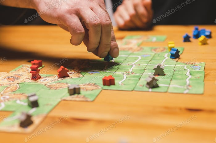 men friends have fun playing the carcassonne board game at night. male hands and game cards and chip
