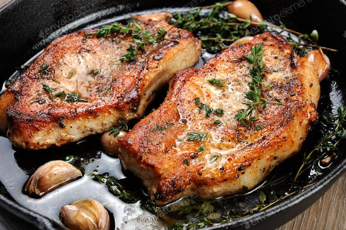 Juicy, browned pork steak on a bone in oil with garlic and herbs in a frying pan. Close-up.