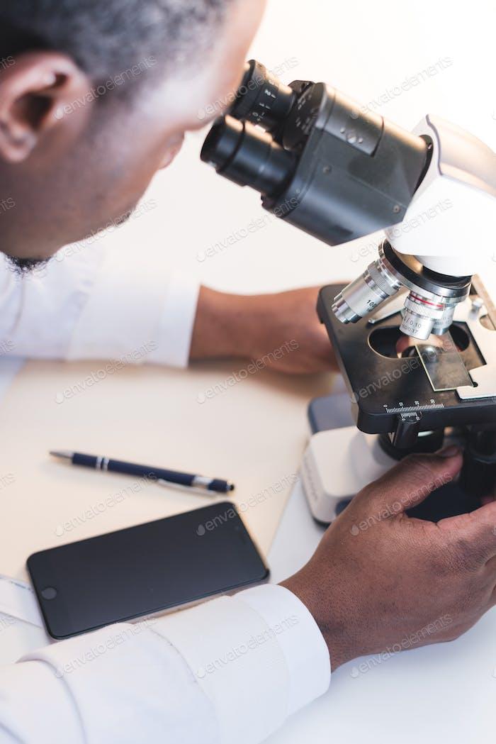 African American scientist using microscope in lab coat