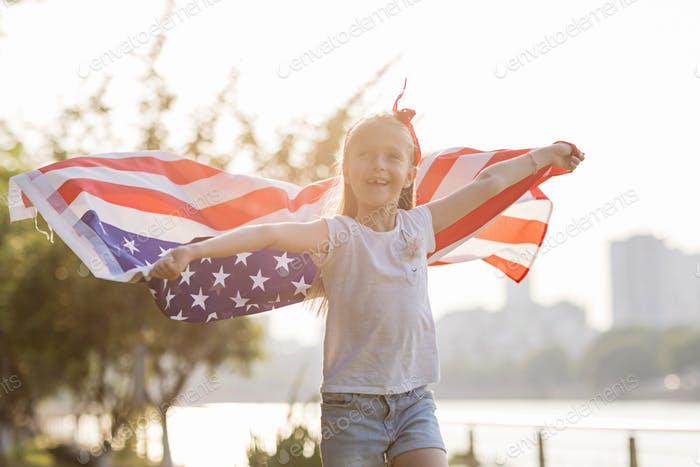 Kid with blonde hair smiling and standing with waving flag of America in park