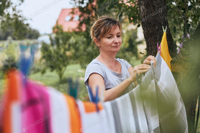Mature woman hanging a freshly laundered bed linen on clothesline stretched between two trees in a