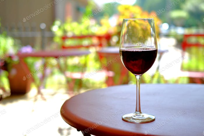 Red wine on the patio with red bistro tables and chairs in the background - copy space
