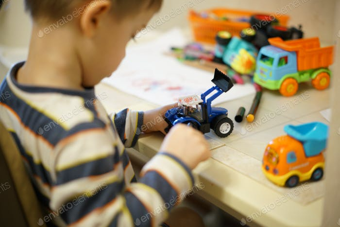 3 year old boy playing with toys and colorful pencils
