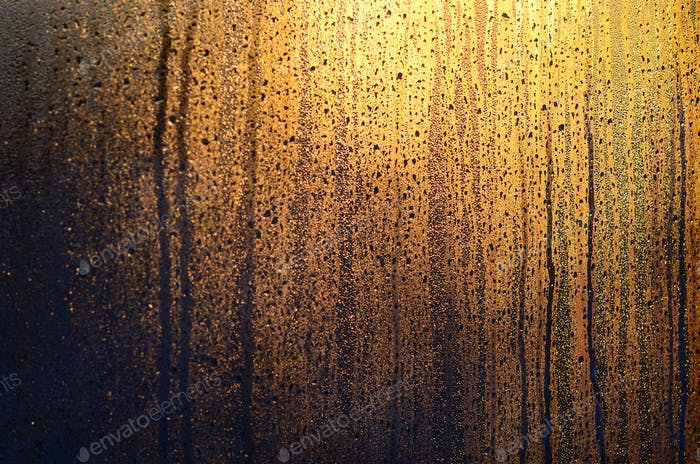 The texture of misted glass with a lot of drops and drips of condensation against the sunlight at