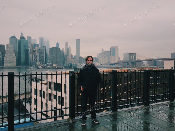 A man standing in front of the NYC skyline on a gloomy day.