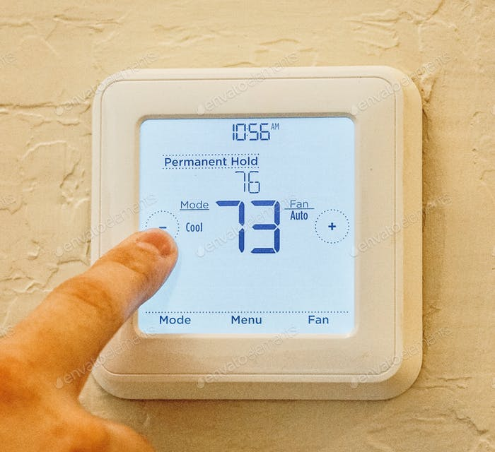Closeup of an adult male finger adjusting the temperature on a thermostat