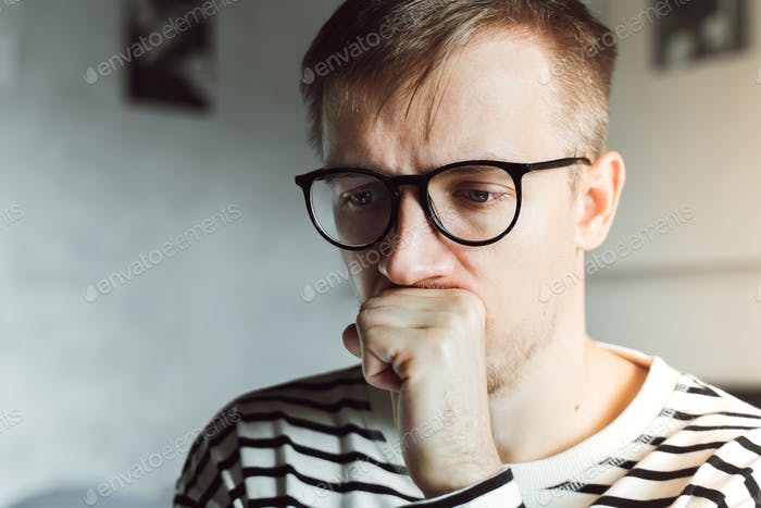 Mental health, anxiety depressed thinking young man in eyeglasses. Healthcare concept