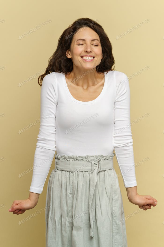 Young woman wait for surprise result announcement with closed eyes, toothy smile, strained shoulders