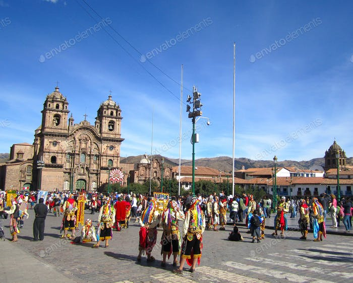 People in colorful traditional clothing in a parade in the main plaza in Cusco
