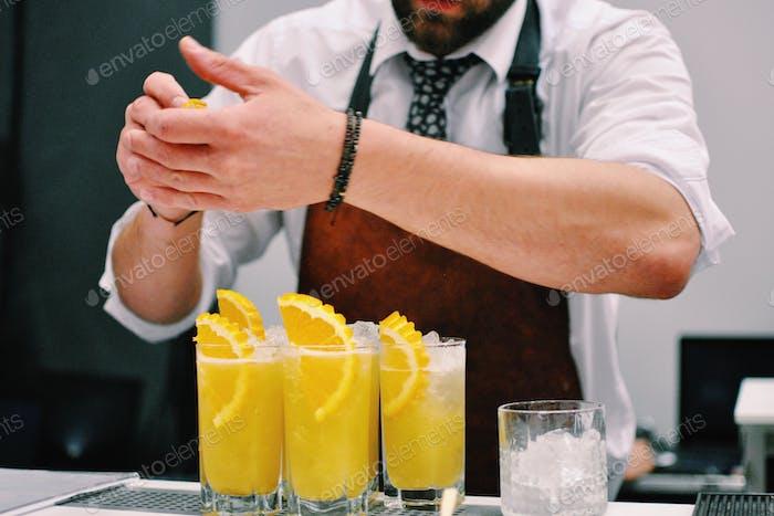 Barkeeper bereitet Orangencocktails vor