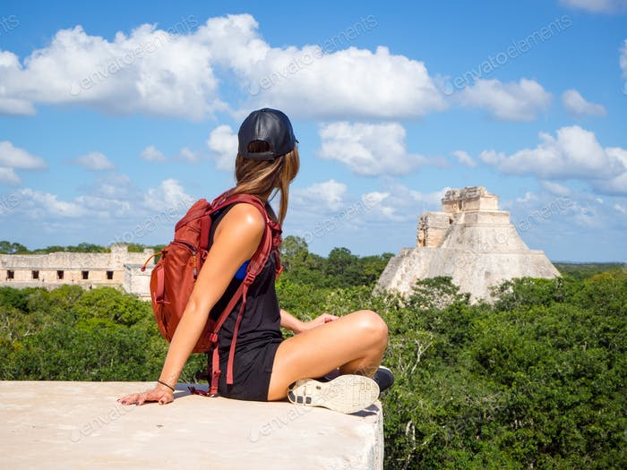 Young woman traveling with backpack in Mexico, exploring the Uxmal mayan ruins in the Yucatan